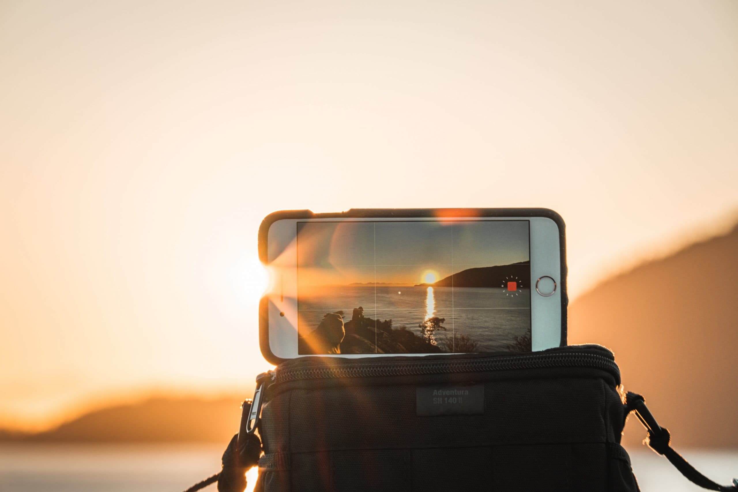 The Best Filmmaking Blogs in 2021 - An image of an iPhone filming a sunset